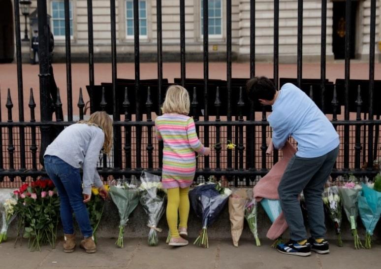 Aficionados reales depositan flores en homenaje al príncipe Felipe frente al Palacio de Buckingham Crédito AP