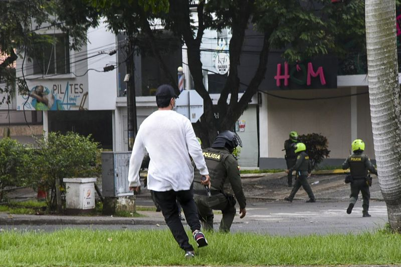 Policías + civiles disparando.