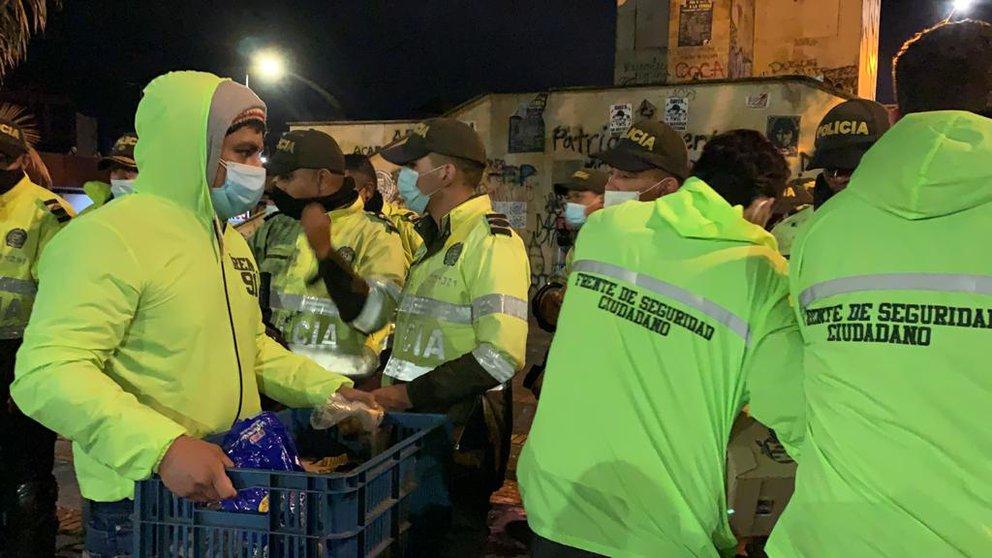 Los jóvenes aguateros le llevan comida a los policías.